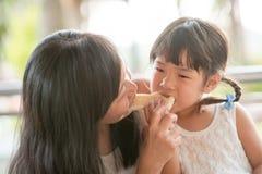 分享面包的妈妈和孩子 库存照片