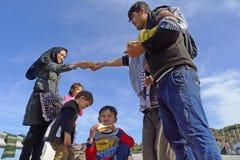 分享面包Lesvos希腊的难民家庭 免版税库存照片