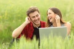 分享从膝上型计算机的愉快的夫妇或朋友音乐 免版税库存图片