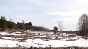 分别地站立在雪原,春天的被放弃的和被毁坏的俄国村庄小屋 股票视频