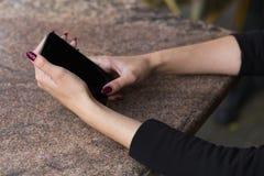 分割在她的手上拿着一个电话一个时髦的女孩的图象 免版税库存图片