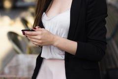 分割在她的手上拿着一个电话一个时髦的女孩的图象 库存照片