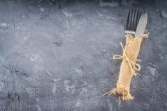 分叉与在袋装的一把刀子在灰色背景 图库摄影