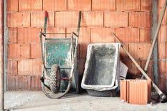 分层堆积与灰浆、手推车和水泥搅拌车的砖在建造场所 库存图片