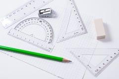 分度器、统治者、铅笔和橡皮擦在方格纸 免版税库存图片