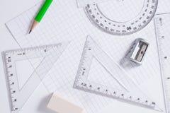 分度器、统治者、铅笔和橡皮擦在方格纸 免版税图库摄影