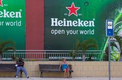 分开坐一名唯一的男人和单身的妇女,他们在Teneriffe等待在Playa las美洲的一辆公共汽车 免版税库存图片