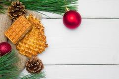 分支与红色球的在粗麻布的圣诞树和奶蛋烘饼在白色木葡萄酒背景 免版税库存图片