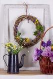 分支和鸡春天花圈与花的在垂悬在前景茶壶的框架的白色背景的有花的 库存照片