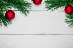 分支圣诞树和玩具球在白色木葡萄酒背景 库存照片