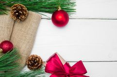 分支圣诞树和礼物盒有丝带的在粗麻布鞠躬在白色木葡萄酒背景 库存图片