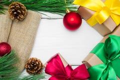 分支圣诞树和礼物盒有丝带的在粗麻布鞠躬在白色木葡萄酒背景 免版税库存图片