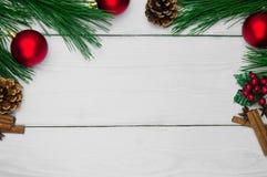 分支圣诞树和红色球与锥体和肉桂条在白色木背景 免版税库存图片