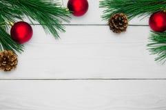 分支圣诞树和红色球与锥体在白色木葡萄酒背景 库存照片