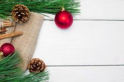 分支圣诞树和红色球用桂香在粗麻布在白色木葡萄酒背景 免版税库存图片