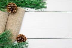 分支圣诞树和锥体在粗麻布在白色木葡萄酒背景 免版税图库摄影