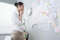 分析一张财政图的女实业家 免版税图库摄影