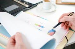 分析一张财政图表的商人 免版税库存图片