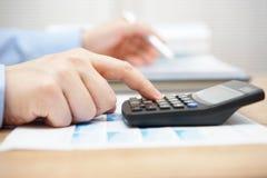 分析企业数据和使用计算器的商人 免版税库存图片