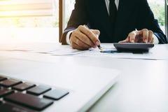 分析关于图的商人报告与计算器在办公室 免版税图库摄影
