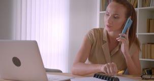 分析关于膝上型计算机谈话的典雅的白种人女实业家数据在手机和在是的笔记本写繁忙的在办公室 股票视频