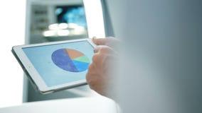 分析和看图表和图在片剂的工友在现代hightech办公室 特写镜头概念 股票录像
