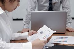 分析图或文书工作的被注重的亚裔女商人在会议期间在会议室 库存照片