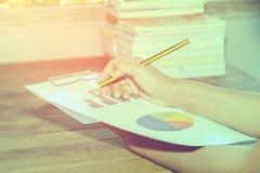 分析在一张木书桌上的商人企业图 库存图片