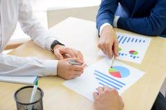 分析在图表的商人财务成果在表附近在现代办公室 背景黑色五颜六色的概念玩偶小组工作 图库摄影