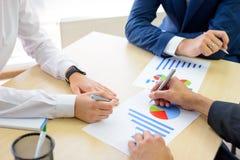分析在图表的商人财务成果在表附近在现代办公室 背景黑色五颜六色的概念玩偶小组工作 免版税库存照片