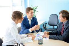 分析在图表的商人财务成果在表附近在现代办公室 背景黑色五颜六色的概念玩偶小组工作 免版税库存图片