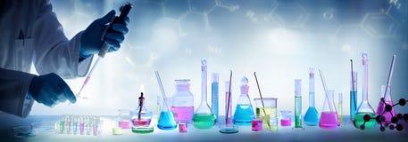 分析实验室-有吸移管和烧杯的科学家 图库摄影