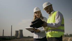 分析工业领域计划和完成在剪贴板工作进展报告的工程师和工头在油气精炼厂附近- 影视素材