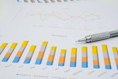 分析投资图的商人在他的工作场所 免版税库存图片