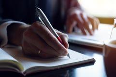 分析投资图的商人 应计额 采取笔记的财政经理的手,当工作时 库存图片