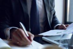 分析投资图的商人 应计额 采取笔记的财政经理的手,当工作时 免版税库存照片