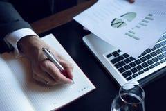 分析投资图的商人 应计额 采取笔记的财政经理的手,当工作时 免版税图库摄影