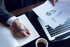 分析投资图的商人 应计额 采取笔记的财政经理的手,当工作时 库存照片