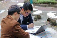 分析数据的严肃的商人在会议期间在公开室外 免版税库存照片