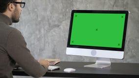 分析数据的典雅的商人在他的计算机上的办公室 对显示器的后面看法 绿色屏幕大模型显示 股票录像