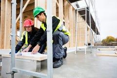 分析文件的木匠在建造场所 免版税库存照片