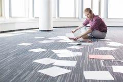 分析照片的商人,当坐地板在创造性的办公室时 免版税库存照片