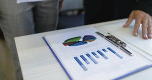 分析财务数据举行报告文件商人的商人和女实业家讨论市场事 股票录像