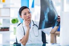 分析X-射线的被集中的医生 免版税库存照片
