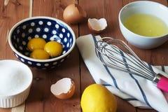 分离鸡蛋和和准备卵黄质在一点碗的扫的蛋白和卵黄质 图库摄影
