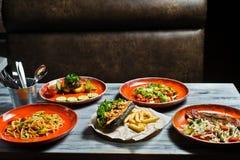 分类各种各样的食物格栅、肉、bbq党费斯特热狗、烤肉排骨、牛排、Carbonara浆糊和螃蟹沙拉 库存照片