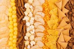 分类嘎吱咬嚼的快餐-玉米花,烤干酪辣味玉米片,油煎方型小面包片,玉米黏附,土豆片作为装饰背景,顶视图,特写镜头 免版税图库摄影