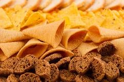 分类嘎吱咬嚼的快餐-玉米花,烤干酪辣味玉米片,油煎方型小面包片,玉米黏附,土豆片作为装饰条纹背景,特写镜头 免版税库存图片
