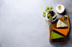 分类艰苦,不很软和软干酪用橄榄, grissini面包条,雀跃,葡萄,在灰色混凝土 图库摄影