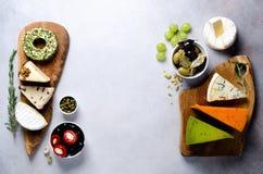 分类艰苦,不很软和软干酪用橄榄, grissini面包条,雀跃,葡萄,在灰色混凝土 库存图片